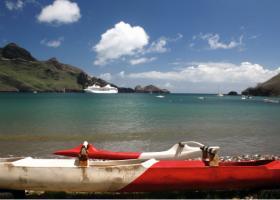 """Une pirogue à balancier et le moderne paquebot """"Paul Gauguin"""", un des navires que les habitants de Nuku Hiva aimeraient voir plus souvent dans leurs eaux."""